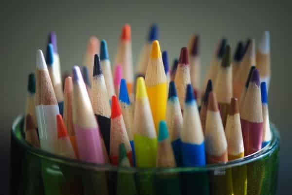 crayons de couleurs dans un pot en verre pointes tournées vers le haut