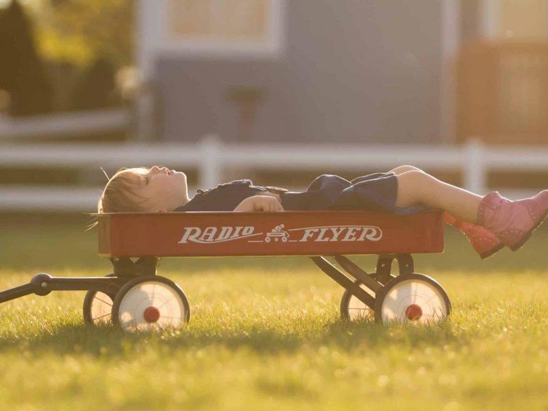 enfant allongé dans une remorque jouet
